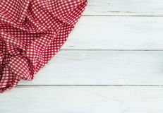 Crumpled red checkered tablecloth or napkin on empty white wood. The Crumpled red checkered tablecloth or napkin on empty white wooden table with copy space for Royalty Free Stock Photography