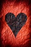 Crumpled red paper with black heart Stock Photos