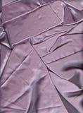 Crumpled satin fabric. Satin texture. Light purple background. royalty free stock image