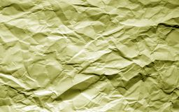 Crumpled sheet of paper with blur effect in yellow tone. Stock Photography
