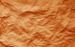 Crumpled sheet of paper in orange color. Abstract background and texture for design, surface, isolated, pattern, old, wallpaper, vintage, retro, decorative stock image