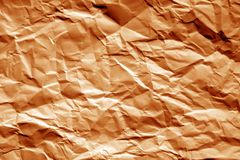 Crumpled sheet of paper in orange tone. Stock Photo