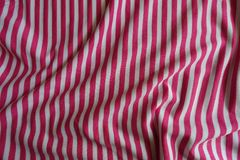 Crumpled striped fabric in pink and white. From above Royalty Free Stock Photo