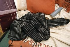 Crumpled sweater on sofa. Crumpled sweater, pillows and blanket left in mess on the sofa royalty free stock photography