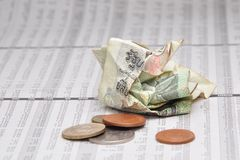 Crumpled Thai banknote and small change on stock quotes. Sheet stock image