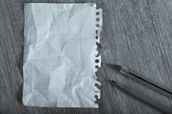 Crumpled torn page. Empty crumpled page torn from notebook lying on wooden surface royalty free stock photography