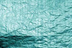 Crumpled transparent plastic surface in cyan color. Abstract background and texture for design stock photography