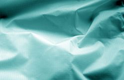 Crumpled transparent plastic surface in cyan color. Abstract background and texture for design stock image