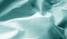 Crumpled transparent plastic surface in cyan color. Abstract background and texture for design stock photos