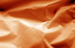 Crumpled transparent plastic surface in orange color. Abstract background and texture for design royalty free stock images