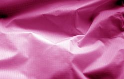 Crumpled transparent plastic surface in pink color. Abstract background and texture for design stock photo