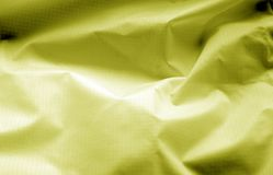Crumpled transparent plastic surface in yellow color. Abstract background and texture for design stock photography