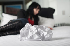 Crumpled up break up letter. Sitting discarded on a bed with woman in background royalty free stock image