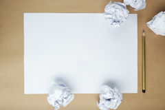 Crumpled up papers with a sheet of blank paper and a pencil on brown background. Stock Images