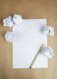 Crumpled up papers with a sheet of blank paper and a pencil on brown background. Royalty Free Stock Photos