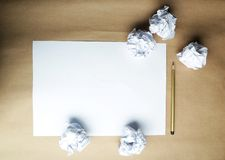 Crumpled up papers with a sheet of blank paper and a pencil on brown background. Stock Photo