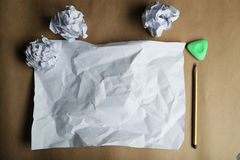 Crumpled up papers with a sheet of blank paper and a pencil on brown background. Royalty Free Stock Images