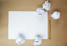 Crumpled up papers with a sheet of blank paper and a pencil on brown background. Stock Image