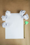 Crumpled up papers with a sheet of blank paper and a pencil on the brown background Royalty Free Stock Photography