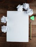 Crumpled up papers with a sheet of blank paper and a pencil on brown wooden background. Stock Image