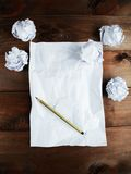 Crumpled up papers with a sheet of blank paper and a pencil on brown wooden background. Royalty Free Stock Photo