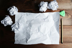 Crumpled up papers with a sheet of blank paper and a pencil on brown wooden background. Stock Images