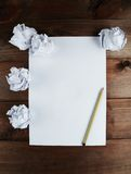 Crumpled up papers with a sheet of blank paper and a pencil on brown wooden background. Royalty Free Stock Photography