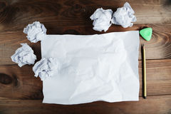 Crumpled up papers with a sheet of blank paper and a pencil on brown wooden background. Royalty Free Stock Image
