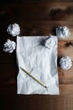 Crumpled up papers with a sheet of blank paper and a pencil on a brown wooden background Royalty Free Stock Image