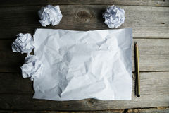Crumpled up papers with a sheet of blank paper and a pencil on grey wooden background. Stock Photo