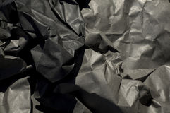 Crumpled Up Thick Black Paper. Close up of thick black semi gloss paper crumpled up with harsh shadows Stock Photos