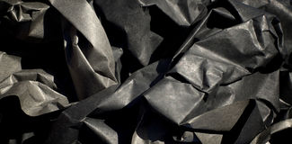 Crumpled UpThick Black Paper. Close up of thick black semi gloss paper crumpled up with harsh shadows Royalty Free Stock Images