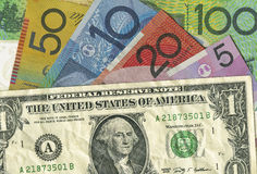 A crumpled US dollar bill over Australian money. A crumpled US dollar bill over Australian dollars showing its decline in value. Copyspace Royalty Free Stock Photo