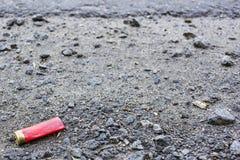 Crumpled usou o cartucho da espingarda no asfalto fotografia de stock royalty free