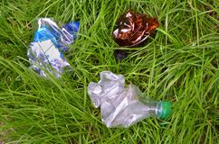 Crumpled plastic bottles lie on the grass, garbage in the grass closeup royalty free stock image