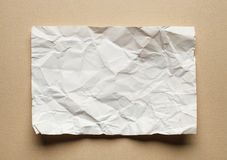 Crumpled  white paper card on beige background Stock Photography