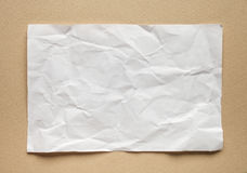 Crumpled  white paper card on beige background Stock Photos