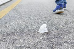 Crumpled white plastic cup on an asphalt road with a yellow stripe. In the background are the legs of a departing person who threw trash royalty free stock images