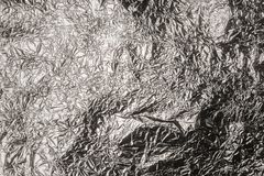 Crumpled wrinkled silver foil texture. Closeup bright material royalty free stock image
