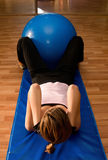 Crunches with a Pilates Ball. A woman exercising with a pilates ball between her legs Royalty Free Stock Photo