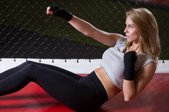 Crunches with punch. Young strong woman doing crunches with punch at gym royalty free stock images