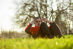 Crunches. Young sportsman working-out in a park, doing a series of crunches Stock Photos