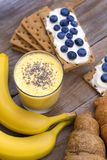 Crunchy cereal breakfast, banana smoothie. Close-up crunchy breads covered by ricotta cheese with blueberries stock images