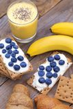 Crunchy cereal breakfast, banana smoothie. Close-up crunchy breads covered by ricotta cheese with blueberries stock photo