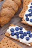 Crunchy cereal breakfast, ricotta cheese and blueberries. Close-up crunchy breads covered by ricotta cheese with blueberries royalty free stock photos