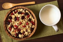 Crunchy Cereal with Dried Berries. Crunchy oatmeal cereal with almond and dried goji berries and cranberries in wooden bowl with a cup of milk on the side stock photos