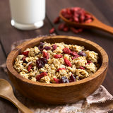 Crunchy Cereal with Dried Berries. Crunchy oatmeal cereal with almond and dried goji berries and cranberries in wooden bowl, photographed with natural light ( stock images
