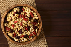 Crunchy Cereal with Dried Berries. Crunchy oatmeal cereal with almond and dried goji berries and cranberries in wooden bowl, photographed overhead on dark wood stock photography