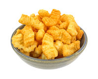 Crunchy cheddar cheese snacks in bowl Royalty Free Stock Image