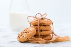 Crunchy cookie with chocolate chips tied in stack on craft baking paper with glass bottle of fresh rustic milk stock images
